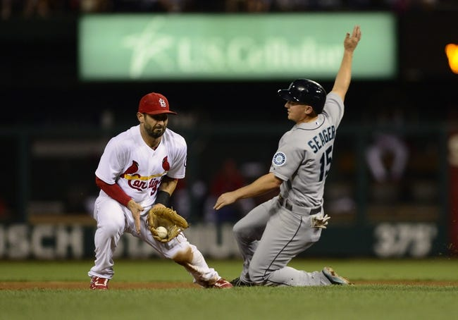 Sep 13, 2013; St. Louis, MO, USA; St. Louis Cardinals shortstop Daniel Descalso (33) fields a throw as Seattle Mariners third baseman Kyle Seager (15) steals second during the sixth inning at Busch Stadium. St. Louis defeated Seattle 2-1 in 10 innings. Mandatory Credit: Jeff Curry-USA TODAY Sports
