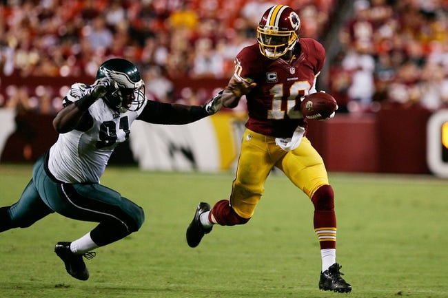 Sep 9, 2013; Landover, MD, USA; Washington Redskins quarterback Robert Griffin III (10) runs with the ball past Philadelphia Eagles defensive tackle Fletcher Cox (91) at FedEx Field. Mandatory Credit: Geoff Burke-USA TODAY Sports
