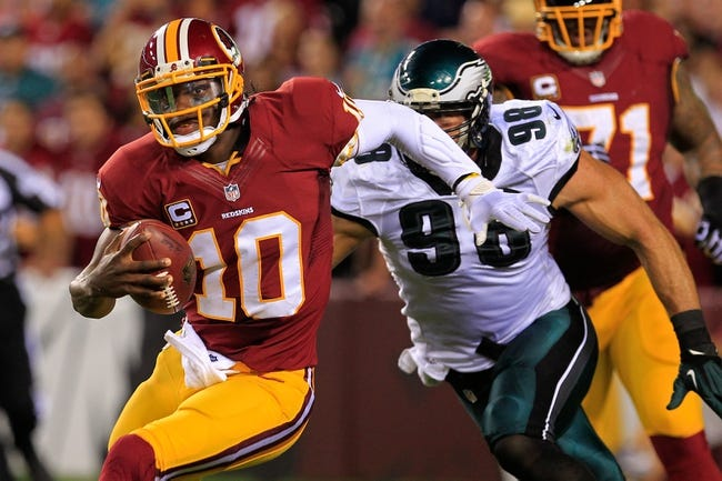 Sep 9, 2013; Landover, MD, USA; Washington Redskins quarterback Robert Griffin III (10) runs with the ball as Philadelphia Eagles outside linebacker Connor Barwin (98) chases at FedEx Field. Mandatory Credit: Geoff Burke-USA TODAY Sports