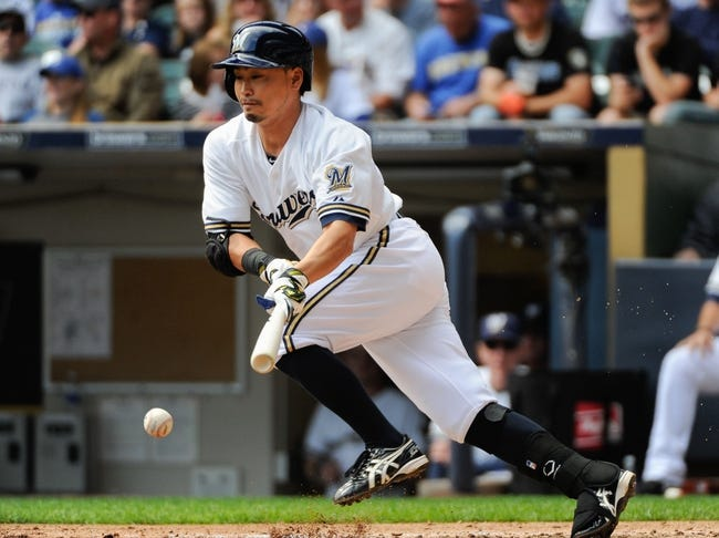 Sep 14, 2013; Milwaukee, WI, USA;  Milwaukee Brewers right fielder Norichika Aoki tries to get on base with a bunt but was out on a close play at first in the third inning during the game against the Cincinnati Reds at Miller Park. Mandatory Credit: Benny Sieu-USA TODAY Sports