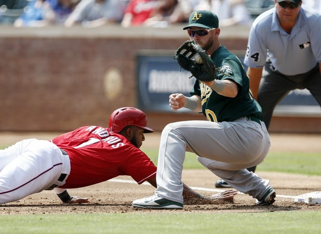 Sep 14, 2013; Arlington, TX, USA; Texas Rangers shortstop Elvis Andrus (1) dives back to first ahead of the throw to Oakland Athletics first baseman Daric Barton (10) during the first inning of a baseball game at Rangers Ballpark in Arlington. Mandatory Credit: Jim Cowsert-USA TODAY Sports