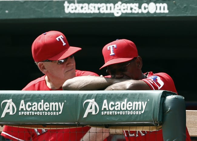 Sep 14, 2013; Arlington, TX, USA; Texas Rangers manager Ron Washington (right) along with bench coach Jackie Moore (4) look on from the dugout against the Oakland Athletics during the first inning of a baseball game at Rangers Ballpark in Arlington. Mandatory Credit: Jim Cowsert-USA TODAY Sports