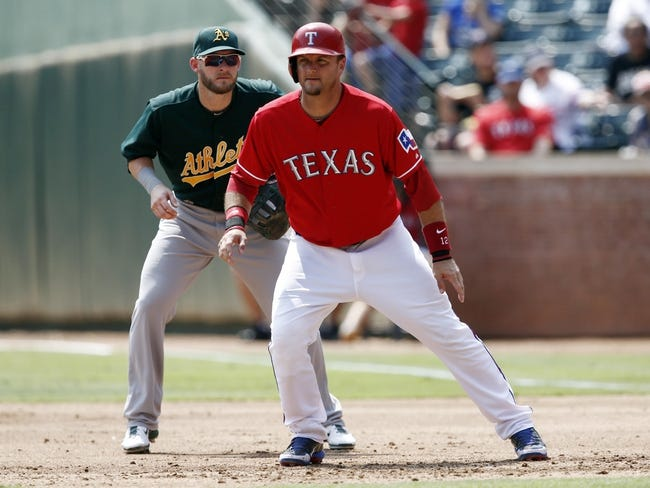 Sep 14, 2013; Arlington, TX, USA; Texas Rangers designated hitter A.J. Pierzynski (12) takes a lead off first in front of Oakland Athletics first baseman Daric Barton (10) during the second inning of a baseball game at Rangers Ballpark in Arlington. Mandatory Credit: Jim Cowsert-USA TODAY Sports