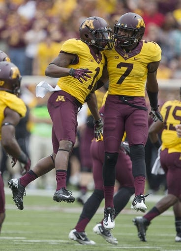 Sep 14, 2013; Minneapolis, MN, USA; Minnesota Golden Gophers wide receiver K.J. Maye (1) celebrates with defensive back Damarius Travis (7) after running a punt return during the fourth quarter at TCF Bank Stadium. The Gophers won 29-12. Mandatory Credit: Jesse Johnson-USA TODAY Sports