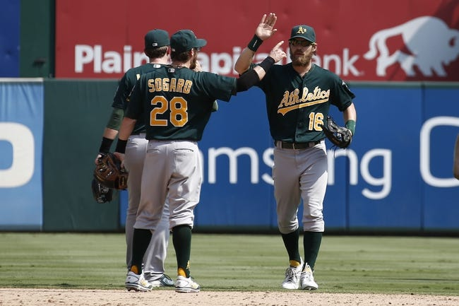 Sep 14, 2013; Arlington, TX, USA; Oakland Athletics second baseman Eric Sogard (28) and right fielder Josh Reddick (16) congratulate each other after their win against the Texas Rangers in baseball game at Rangers Ballpark in Arlington. The Athletics won 1-0. Mandatory Credit: Jim Cowsert-USA TODAY Sports