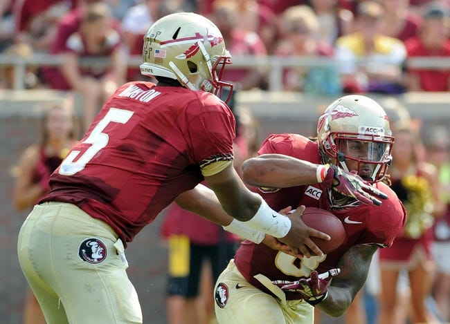 Sep 14, 2013; Tallahassee, FL, USA; Florida State Seminoles quarterback Jameis Winston (5) hands the ball off to running back Devonta Freeman (8) during the first half of the game against the Nevada Wolf Pack at Doak Campbell Stadium. Mandatory Credit: Melina Vastola-USA TODAY Sports