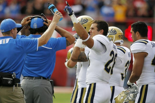 Sep 14, 2013; Lincoln, NE, USA; UCLA Bruins linebacker Taylor Lagace (28) puts his hand in the air after observing a moment of silence for UCLA receiver Nick Pasquale prior to the game against the Nebraska Cornhuskers. Pasquale was struck and killed by a car last Sunday. UCLA won 41-21. Mandatory Credit: Bruce Thorson-USA TODAY Sports