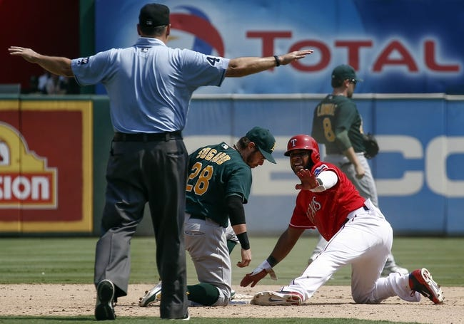 Sep 14, 2013; Arlington, TX, USA; Texas Rangers shortstop Elvis Andrus (1) looks for the call from umpire Andy Fletcher (49) after stealing second base against Oakland Athletics second baseman Eric Sogard (28) during the seventh inning of a baseball game at Rangers Ballpark in Arlington. The Athletics won 1-0. Mandatory Credit: Jim Cowsert-USA TODAY Sports