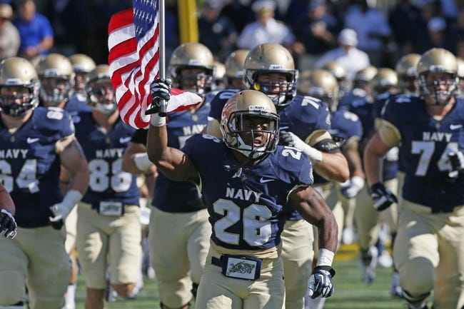 Sep 14, 2013; Annapolis, MD, USA; Navy Midshipmen slotback Marcus Thomas (26) leads his team onto the field prior to the game against the Delaware Blue Hens at Navy Marine Corps Memorial Stadium. Mandatory Credit: Mitch Stringer-USA TODAY Sports
