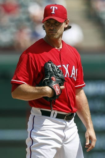 Sep 14, 2013; Arlington, TX, USA; Texas Rangers relief pitcher Neal Cotts (56) looks for the signal against the Oakland Athletics during the ninth inning of a baseball game at Rangers Ballpark in Arlington. The Athletics won 1-0. Mandatory Credit: Jim Cowsert-USA TODAY Sports