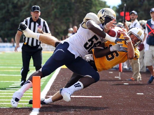 Sep 14, 2013; Laramie, WY, USA; Wyoming Cowboys quarterback Brett Smith (16) is hit by Northern Colorado Bears linebacker Clarence Bumpas (56) during the second half at War Memorial Stadium. Mandatory Credit: Troy Babbitt-USA TODAY Sports