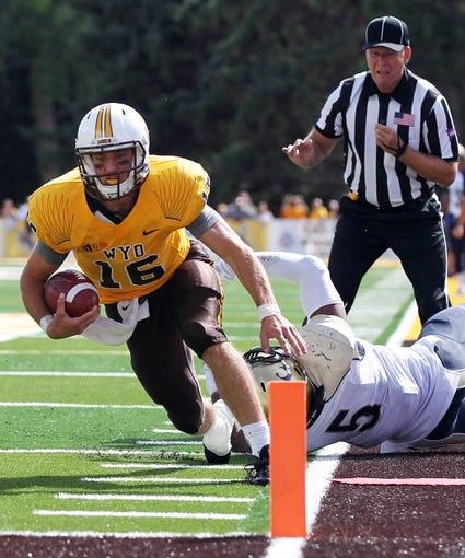 Sep 14, 2013; Laramie, WY, USA; Wyoming Cowboys quarterback Brett Smith (16) avoids Northern Colorado Bears cornerback Brandon Lenoir (6) during the second half at War Memorial Stadium. Mandatory Credit: Troy Babbitt-USA TODAY Sports