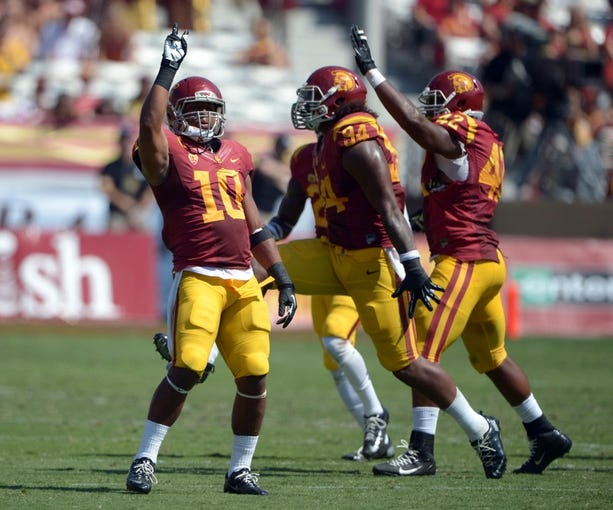 Sep 14, 2013; Los Angeles, CA, USA; Southern California Trojans linebacker Hayes Pullard (10) and defensive end Leonard Williams (94) and linebacker Devon Kennard (42) celebrate during the game against the Boston College Eagles at Los Angeles Memorial Coliseum. USC defeated Boston College 35-7. Mandatory Credit: Kirby Lee-USA TODAY Sports