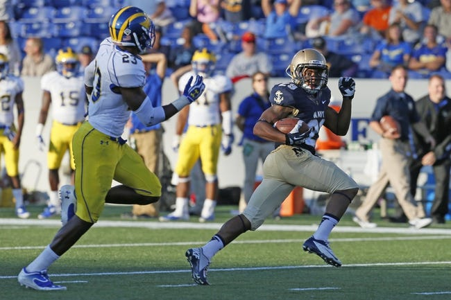 Sep 14, 2013; Annapolis, MD, USA; Navy Midshipmen slotback Geoffrey Whiteside (29) gains yardage past Delaware Blue Hens defensive back Mario Rowson (23) at Navy Marine Corps Memorial Stadium. Mandatory Credit: Mitch Stringer-USA TODAY Sports