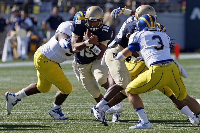 Sep 14, 2013; Annapolis, MD, USA; Navy Midshipmen quarterback Keenan Reynolds (19) runs through the middle of the Delaware Blue Hens defense at Navy Marine Corps Memorial Stadium. Mandatory Credit: Mitch Stringer-USA TODAY Sports