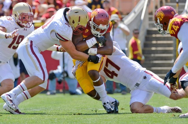 Sep 14, 2013; Los Angeles, CA, USA; USC Trojans wide receiver Darreus Rogers (84) is tackled by Boston College Eagles linebacker Mike Strizak (30) and defensive back Spenser Rositano (47) during first half action at Los Angeles Memorial Coliseum. The Eagles lost 35-7 to the Trojans. Mandatory Credit: Robert Hanashiro-USA TODAY Sports