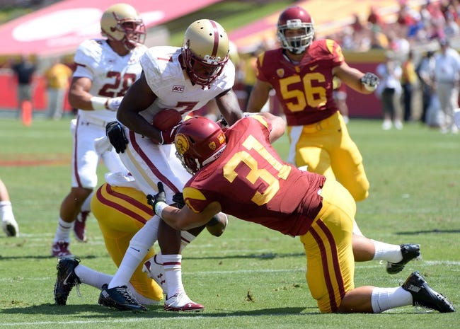 Sep 14, 2013; Los Angeles, CA, USA; Boston College Eagles wide receiver Spiffy Evans (7) is tackled by USC Trojans cornerback Kevon Seymour (13) and Soma Vainuku (31) during a first half kick off  at Los Angeles Memorial Coliseum. The Trojans went on to a 35-7 win.Mandatory Credit: Robert Hanashiro-USA TODAY Sports
