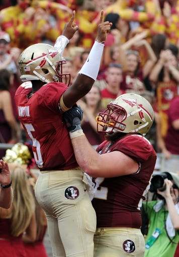 Sep 14, 2013; Tallahassee, FL, USA; Florida State Seminoles quarterback Jameis Winston (5) celebrates a touchdown run with center Brian Stork (52) during the second half of the game against the Nevada Wolf Pack at Doak Campbell Stadium. Mandatory Credit: Melina Vastola-USA TODAY Sports