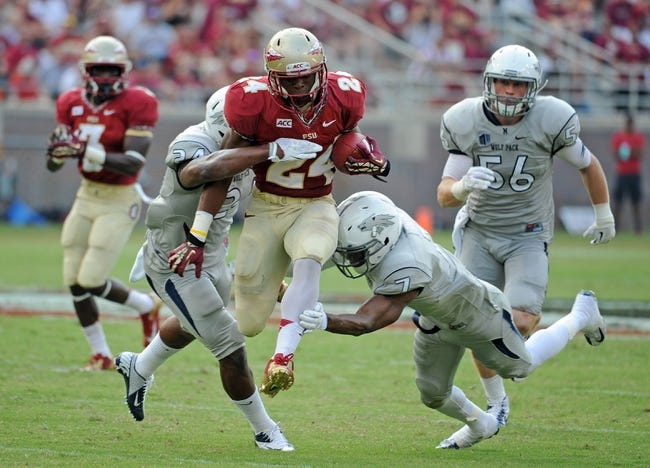 Sep 14, 2013; Tallahassee, FL, USA; Florida State Seminoles running back Ryan Green (24) runs the ball past Nevada Wolf Pack defensive back Markus Smith (7) during the second half of the game at Doak Campbell Stadium. Mandatory Credit: Melina Vastola-USA TODAY Sports