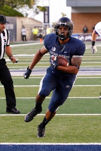 Sep 14, 2013; Logan, UT, USA; Utah State Aggies running back Joey DeMartino (28) runs into the end zone to score a touchdown at Romney Stadium. Mandatory Credit: Chris Nicoll-USA TODAY Sports
