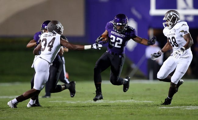 Sep 14, 2013; Evanston, IL, USA; Northwestern Wildcats running back Treyvon Green (22) runs between Western Michigan Broncos defenders during the first quarter at Ryan Field. Mandatory Credit: Jerry Lai-USA TODAY Sports