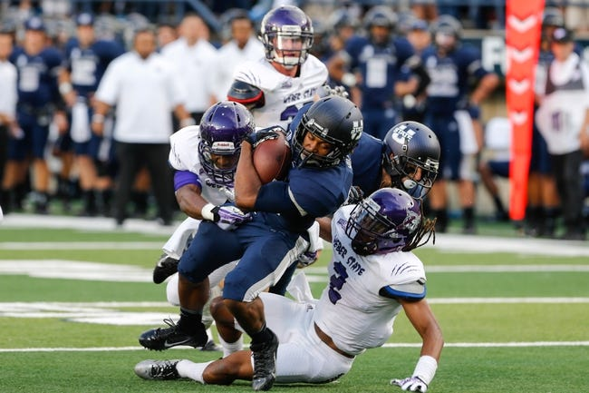 Sep 14, 2013; Logan, UT, USA; Utah State Aggies running back Joe Hill (32) is tackled by Weber State Wildcats cornerback Cordero Dixon (2) during the first quarter at Romney Stadium. Mandatory Credit: Chris Nicoll-USA TODAY Sports