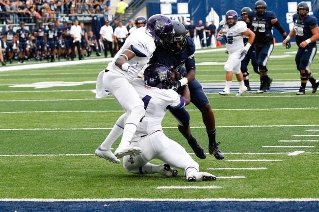 Sep 14, 2013; Logan, UT, USA; Utah State Aggies wide receiver Ronald Butler (18) runs over Weber State Wildcats safety Chris Jones (4) and Weber State Wildcats cornerback Robbie Diamond (6) to score a touchdown during the second quarter at Romney Stadium. Mandatory Credit: Chris Nicoll-USA TODAY Sports