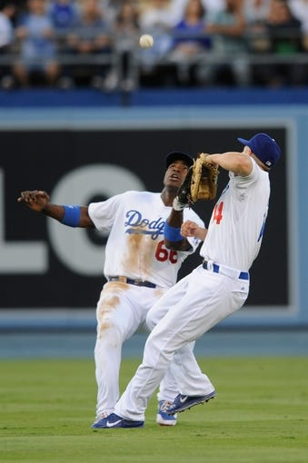 Sep 14, 2013; Los Angeles, CA, USA; Los Angeles Dodgers center fielder Yasiel Puig (66) and Los Angeles Dodgers second baseman Mark Ellis (14) run into each other while chasing a fly ball during the second inning at Dodger Stadium. Mandatory Credit: Kelvin Kuo-USA TODAY Sports