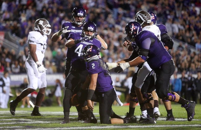 Sep 14, 2013; Evanston, IL, USA; Northwestern Wildcats quarterback Kain Colter (2) is congratulated by teammates after scoring a touchdown against the Western Michigan Broncos during the second quarter at Ryan Field. Mandatory Credit: Jerry Lai-USA TODAY Sports