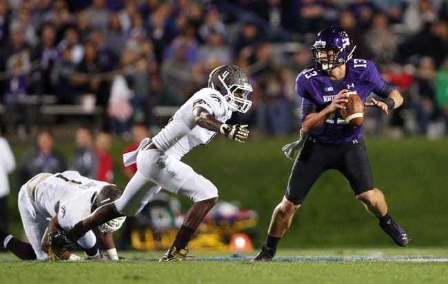 Sep 14, 2013; Evanston, IL, USA; Northwestern Wildcats quarterback Trevor Siemian (13) is pressured by Western Michigan Broncos linebacker Edward Rolle (4) during the second quarter at Ryan Field. Mandatory Credit: Jerry Lai-USA TODAY Sports