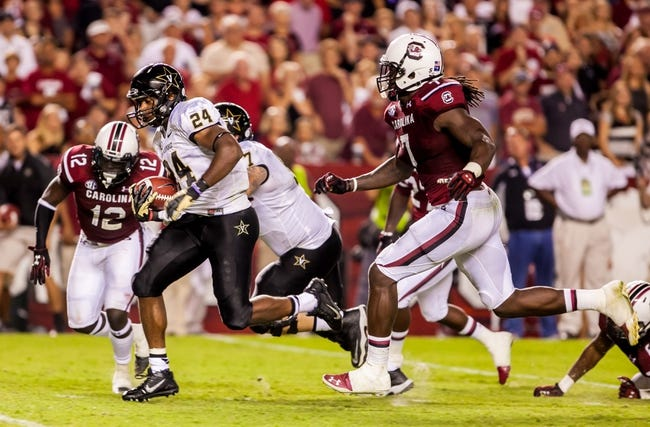 Sep 14, 2013; Columbia, SC, USA; Vanderbilt Commodores running back Wesley Tate (24) rushes for a touchdown as South Carolina Gamecocks defensive end Jadeveon Clowney (7) pursues in the second half at Williams-Brice Stadium. Mandatory Credit: Jeff Blake-USA TODAY Sports