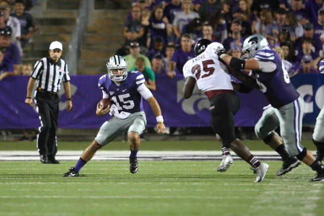 Sep 14, 2013; Manhattan, KS, USA; Kansas State Wildcats quarterback Jake Waters (15) follows the block by offensive linesman BJ Finney (66) on Massachusetts Minutemen defensive back Joe Colton (25) during the Wildcats' 37-7 win at Bill Snyder Family Stadium. Mandatory Credit: Scott Sewell-USA TODAY Sports