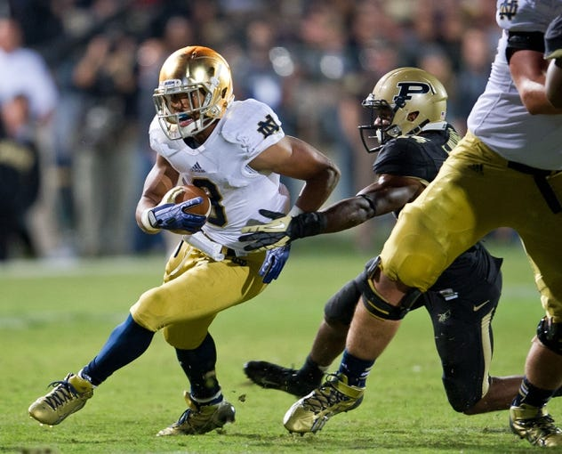 Sep 14, 2013; West Lafayette, IN, USA; Notre Dame Fighting Irish running back Amir Carlisle (3) carries the ball as Purdue Boilermakers cornerback Frankie Williams (24) defends in the third quarter at Ross-Ade Stadium. Notre Dame won 31-24. Mandatory Credit: Matt Cashore-USA TODAY Sports