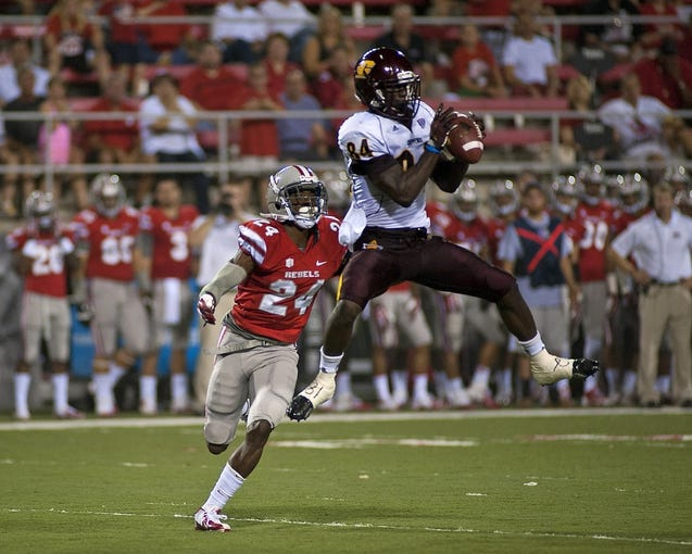Sep 14, 2013; Las Vegas, NV, USA; Central Michigan wide receiver Titus Davis (84) makes a catch in the air on UNLV Rebels defensive back Fred Wilson (24) during an NCAA football game at Sam Boyd Stadium. Mandatory Credit: Stephen R. Sylvanie-USA TODAY Sports