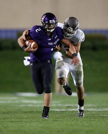 Sep 14, 2013; Evanston, IL, USA; Northwestern Wildcats quarterback Kain Colter (2) is tackled by Western Michigan Broncos safety Justin Currie (33) during the fourth quarter at Ryan Field. Mandatory Credit: Jerry Lai-USA TODAY Sports