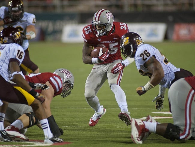 Sep 14, 2013; Las Vegas, NV, USA; UNLV Rebels running back Tim Cornett (35) carries the ball during an NCAA football game against the Central Michigan Chippewas at Sam Boyd Stadium. UNLV won the game 31-21. Mandatory Credit: Stephen R. Sylvanie-USA TODAY Sports