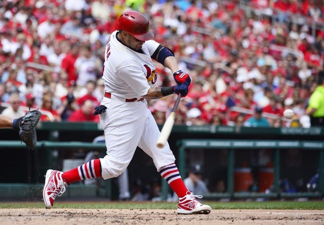 Sep 15, 2013; St. Louis, MO, USA; St. Louis Cardinals catcher Yadier Molina (4) hits a home run against the Seattle Mariners at Busch Stadium. Mandatory Credit: Scott Rovak-USA TODAY Sports