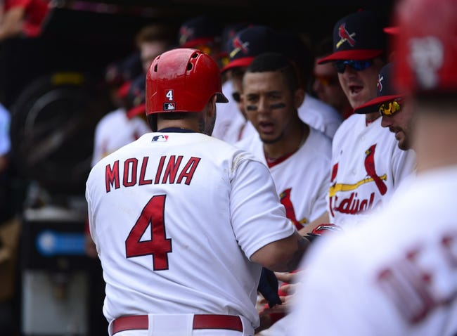 Sep 15, 2013; St. Louis, MO, USA; St. Louis Cardinals catcher Yadier Molina (4) is congratulated after hitting a home run against the Seattle Mariners at Busch Stadium. Mandatory Credit: Scott Rovak-USA TODAY Sports