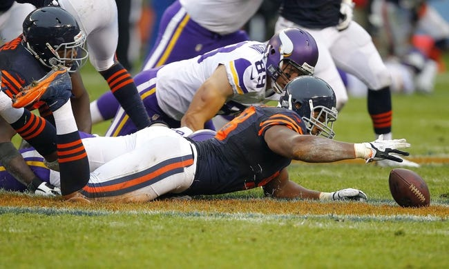 Sep 15, 2013; Chicago, IL, USA; Chicago Bears defensive end Corey Wootton (98) recovers a fumble from Minnesota Vikings running back Adrian Peterson (not pictured) during the second half at Soldier Field. Chicago won 31-30. Mandatory Credit: Dennis Wierzbicki-USA TODAY Sports