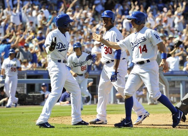 September 15, 2013; Los Angeles, CA, USA; Los Angeles Dodgers relief pitcher Edinson Volquez (30) shortstop Dee Gordon (9), and second baseman Mark Ellis (14) celebrate after scoring runs during the fifth inning against the San Francisco Giants at Dodger Stadium. Mandatory Credit: Gary A. Vasquez-USA TODAY Sports