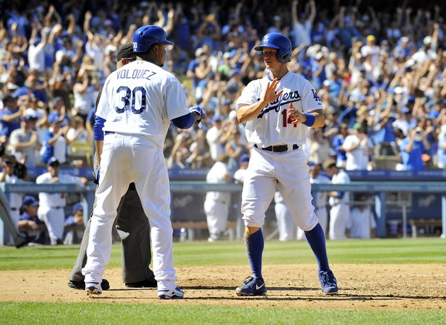 September 15, 2013; Los Angeles, CA, USA; Los Angeles Dodgers relief pitcher Edinson Volquez (30) and second baseman Mark Ellis (14) both celebrate after scoring runs during the fifth inning against the San Francisco Giants at Dodger Stadium. Mandatory Credit: Gary A. Vasquez-USA TODAY Sports