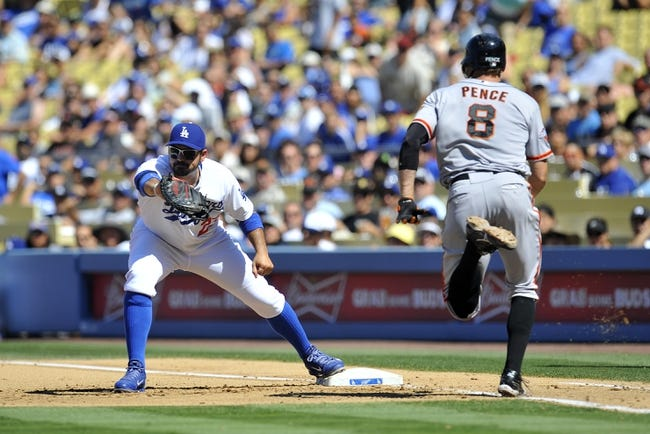 September 15, 2013; Los Angeles, CA, USA; Los Angeles Dodgers first baseman Adrian Gonzalez (23) applies the tag to first to force out San Francisco Giants right fielder Hunter Pence (8) in the fourth inning at Dodger Stadium. Mandatory Credit: Gary A. Vasquez-USA TODAY Sports