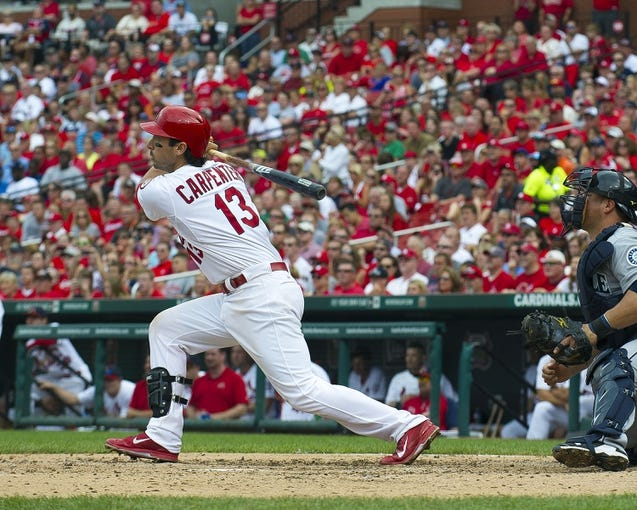 Sep 15, 2013; St. Louis, MO, USA; St. Louis Cardinals second baseman Matt Carpenter (13) hits a 2 rbi single against the Seattle Mariners during the fourth inning at Busch Stadium. The Cardinals defeated the Mariners 12-2. Mandatory Credit: Scott Rovak-USA TODAY Sports
