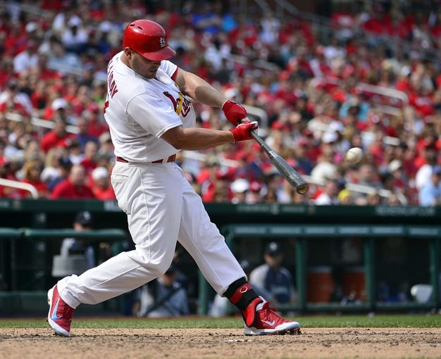 Sep 15, 2013; St. Louis, MO, USA; St. Louis Cardinals left fielder Matt Holliday (7) hits an rbi double against the Seattle Mariners during the seventh inning at Busch Stadium. The Cardinals defeated the Mariners 12-2. Mandatory Credit: Scott Rovak-USA TODAY Sports