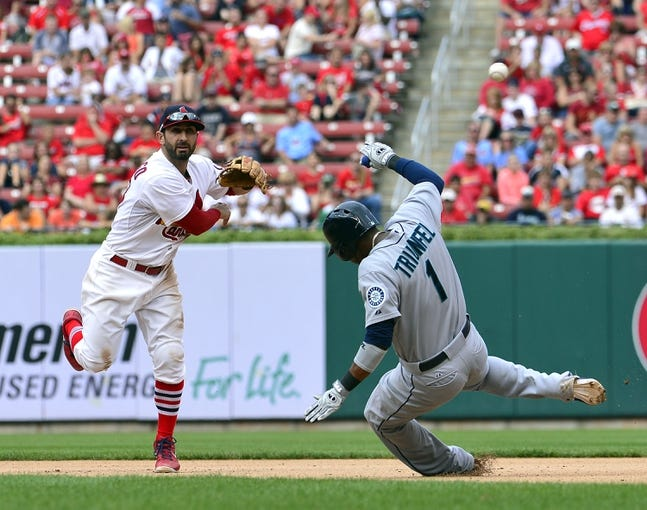 Sep 15, 2013; St. Louis, MO, USA; St. Louis Cardinals shortstop Daniel Descalso (33) turns a double play over Seattle Mariners shortstop Carlos Triunfel (1) during the seventh inning at Busch Stadium. The Cardinals defeated the Mariners 12-2. Mandatory Credit: Scott Rovak-USA TODAY Sports