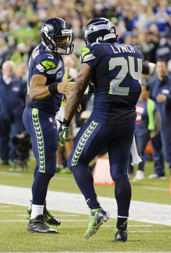 Sep 15, 2013; Seattle, WA, USA; Seattle Seahawks quarterback Russell Wilson (3) and running back Marshawn Lynch (24) celebrate after Lynch scored a touchdown against the San Francisco 49ers at CenturyLink Field. Seattle defeated San Francisco 29-3. Mandatory Credit: Steven Bisig-USA TODAY Sports