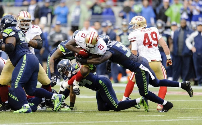 Sep 15, 2013; Seattle, WA, USA; San Francisco 49ers running back Frank Gore (21) tries to break a tackle by Seattle Seahawks strong safety Kam Chancellor (31) during the 1st half at CenturyLink Field. Seattle defeated San Francisco 29-3. Mandatory Credit: Steven Bisig-USA TODAY Sports