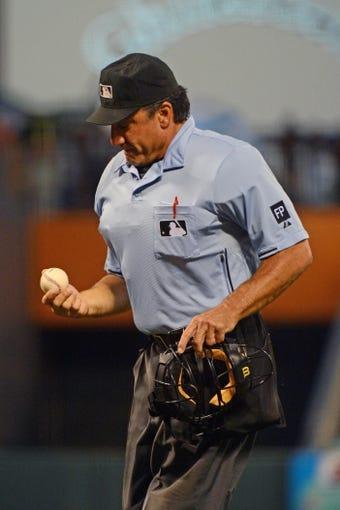September 6, 2013; San Francisco, CA, USA; MLB umpire Phil Cuzzi (10) looks at a baseball during the second inning between the San Francisco Giants and the Arizona Diamondbacks at AT&T Park. The Giants defeated the Diamondbacks 3-0. Mandatory Credit: Kyle Terada-USA TODAY Sports