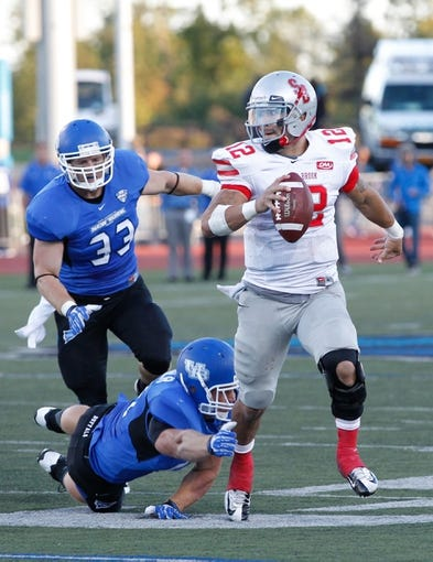 Sep 14, 2013; Buffalo, NY, USA; Stony Brook Seawolves quarterback Lyle Negron (12) breaks a tackle by Buffalo Bulls linebacker Lee Skinner (24) during the game at University of Buffalo Stadium. Buffalo beats Stony Brook 26-23 in OT. Mandatory Credit: Kevin Hoffman-USA TODAY Sports