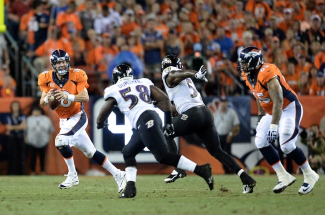 Sep 5, 2013; Denver, CO, USA; Denver Broncos quarterback Peyton Manning (18) runs with the football as Baltimore Ravens outside linebacker Terrell Suggs (55) and linebacker Elvis Dumervil (58) defend at Sports Authority Field at Mile High. Mandatory Credit: Ron Chenoy-USA TODAY Sports